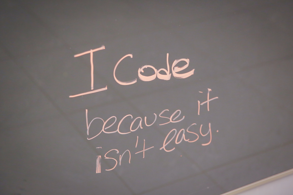 Photo of whiteboard where a student wrote I code because it isn't easy
