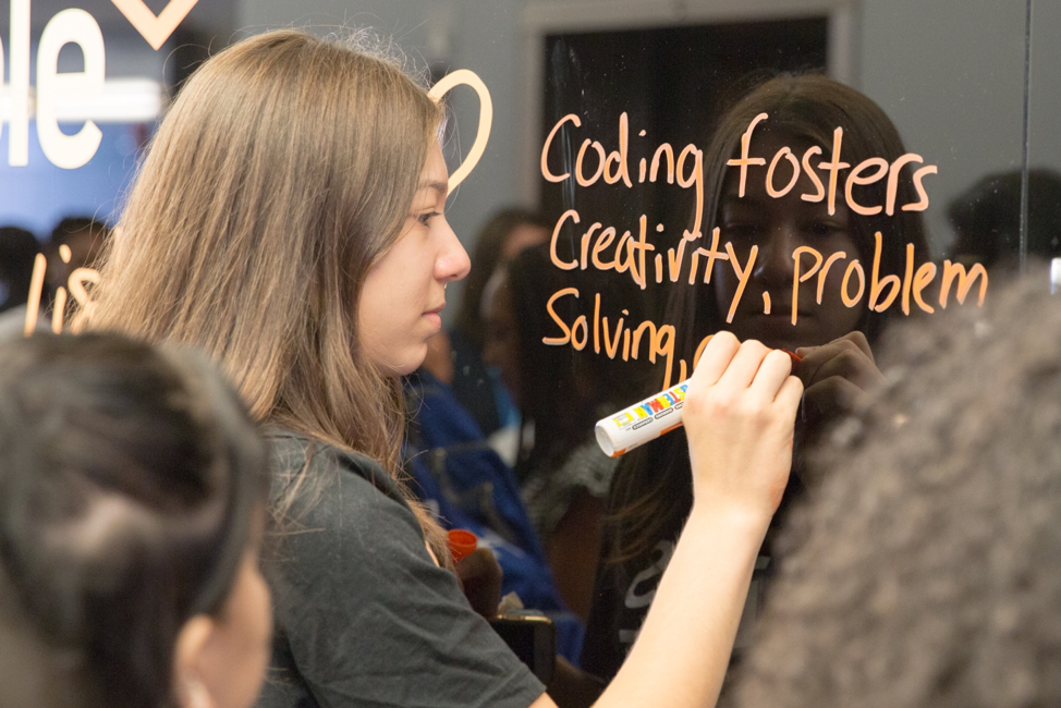 Photo of student from Girls Who Code writing on the whiteboard coding fosters creativity, problem solving