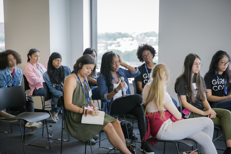 Photo of group of students from Girls Who Code asking questions to the Audible employees