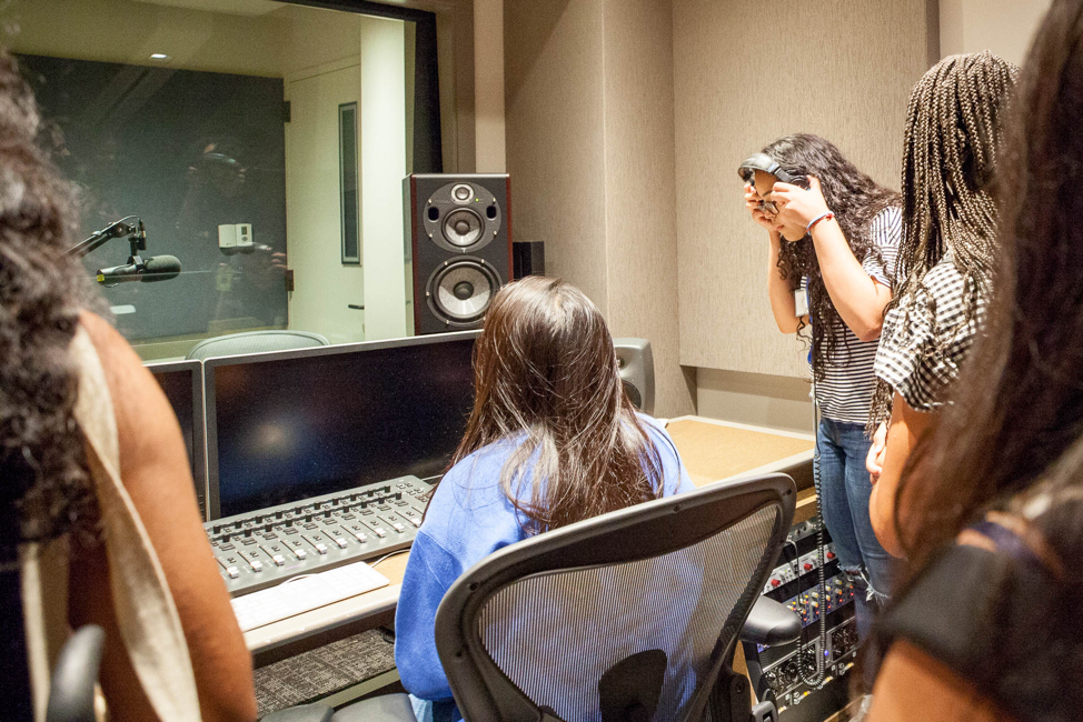 Photo of students in the Audible Studios listening to headphones and sitting in front of recording booth