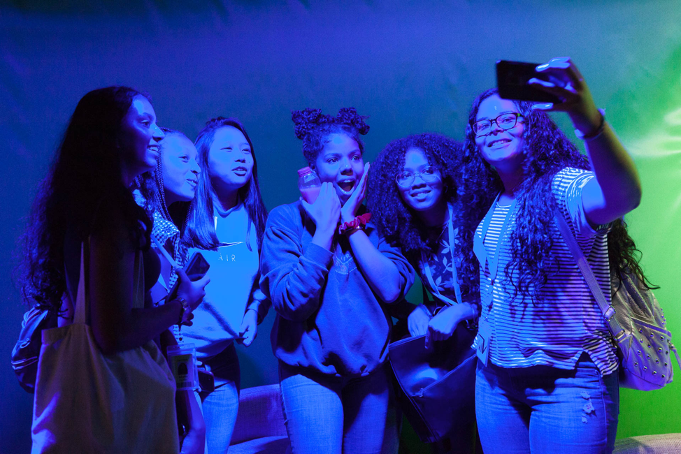 Photo of students in the Audible Studios lounge taking selfie photos